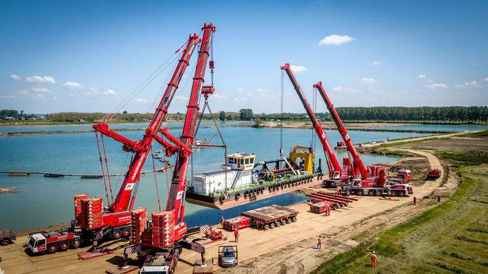 De 300 ton wegende zandzuiger IJsselmeer hangt in de touwen van vier torenkranen op de oever van de zandwinplas-in-wording Geertjesgolf.