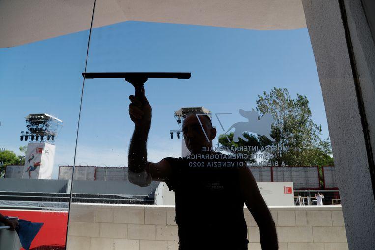De vensters van Cinema Palace aan de Lido van Venetië worden alvast gepoetst voor het filmfestival. Het eerste grote filmfestival in coronatijden roept veel vragen op. Beeld AP