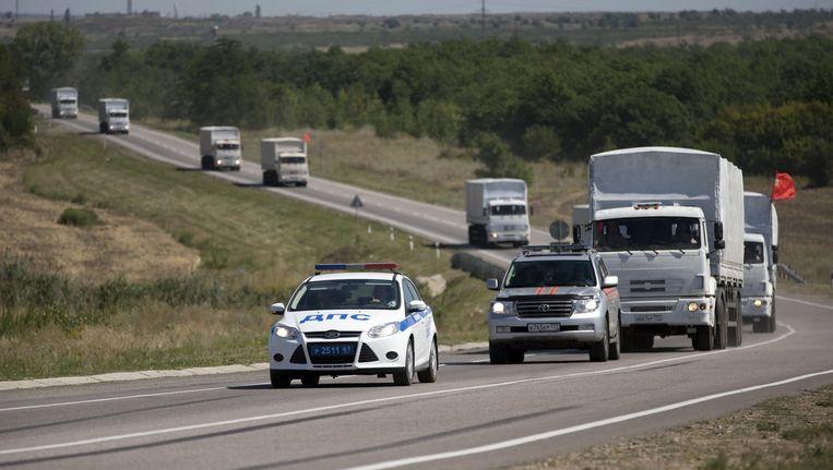 Het hulpkonvooi op weg naar de grens, geëscorteerd door een politieauto. Beeld ap