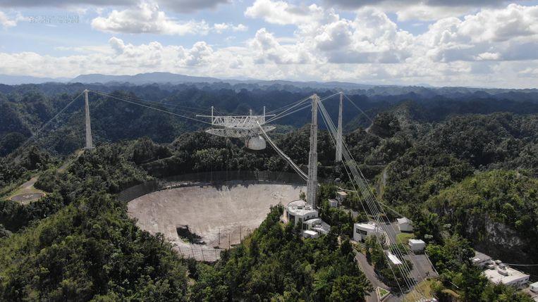 De radiotelescoop Arecibo. Links op de foto is de schade aan de schotel zichtbaar, veroorzaakt door een gebroken kabel.  Beeld Reuters