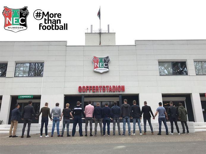 Mannelijke medewerkers na NEC staan in een lange rij hand in hand voor het Goffertstadion.
