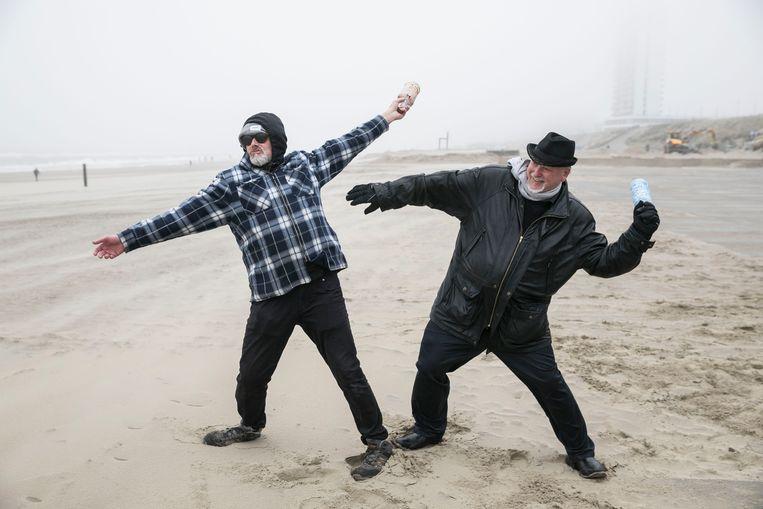 """Kunstenaars Wim Kömhoff en Rob van der Schoor gooien flessenpost voor Boris Johnson in het water. Denken ze dat de boodschap zal aankomen? """"Vast wel.""""  Beeld Amaury Miller"""
