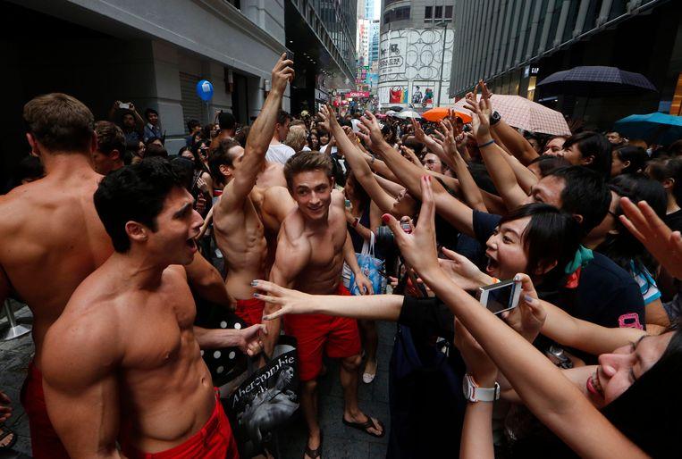 Abercrombie & Fitch-modellen delen cadeautjes uit aan klanten tijdens de opening van een winkel in Hongkong. Beeld ap