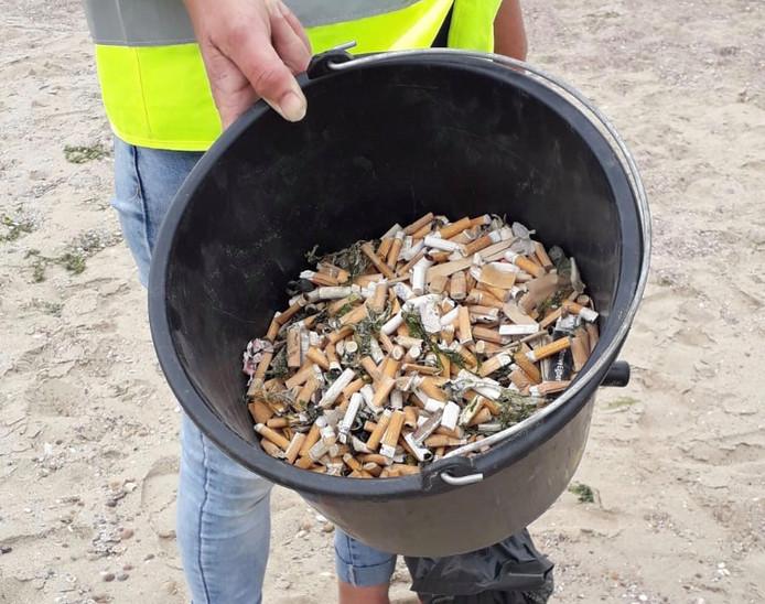 Twee grote emmers sigarettenpeuken zijn al van het strand gehaald.