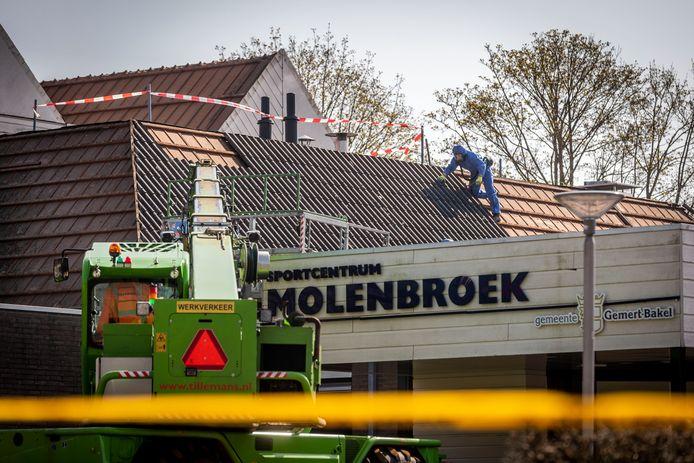 Op het dak van sportpark de Molenbroek in Gemert zijn mannen bezig met asbest verwijderen.