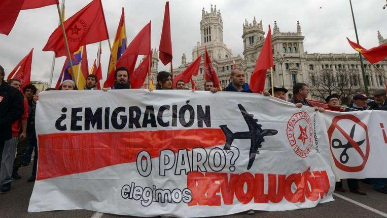 Demonstratie in Madrid ter gelegenheid van de Dag van de Arbeid. Emigreren of werk. Wij kiezen de revolutie, staat op het spandoek te lezen. Beeld afp