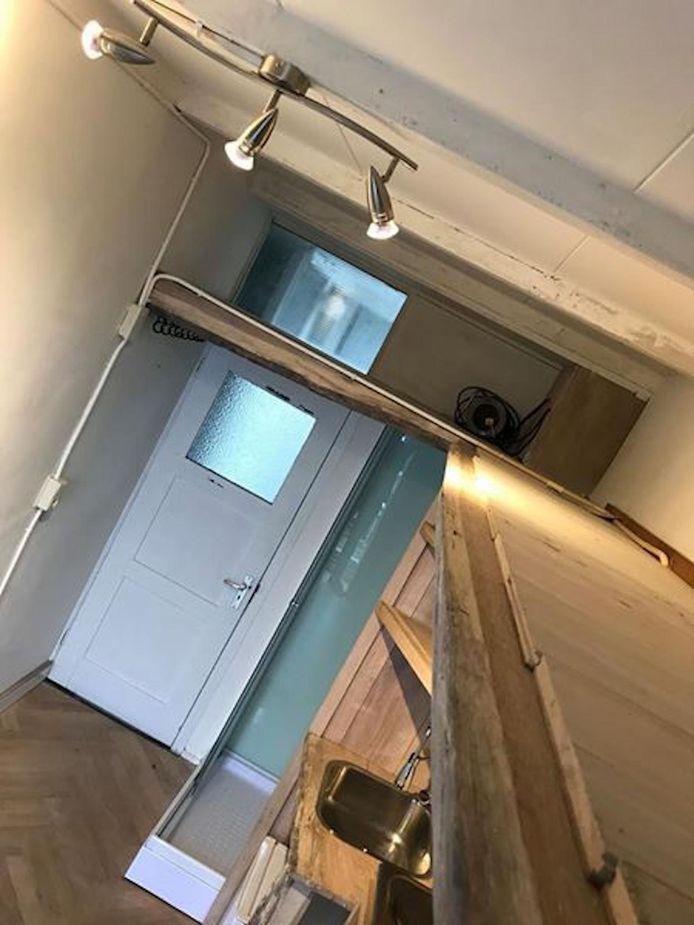 Een foto van het 'appartement' waar op acht vierkante meter een douche is gebouwd en een minikeuken.