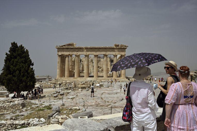 Toeristen in de hitte bij de Akropolis van Athene. Beeld Hollandse Hoogte / AFP
