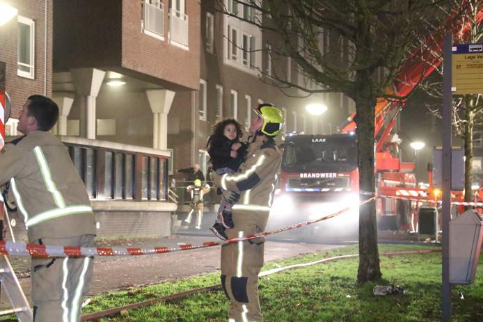 Brandweerlieden ontfermen zich over bewoners tijdens het blussen van een reeks autobranden in Wateringse veld