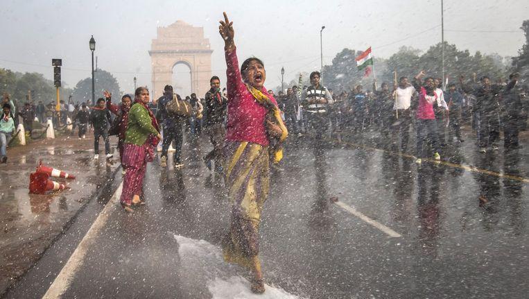 Een Indiase vrouw zet zich schrap voor het water dat de politie afvuurt op een groep demonstranten. De demonstranten protesteren tegen de lakse reactie van de Indiase overheid op recente verkrachtingszaken in het land. Beeld getty
