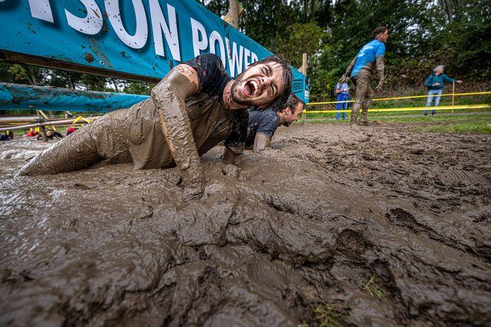 Een deelnemer aan Mud Masters in Biddinghuizen worstelt zich door de modder.
