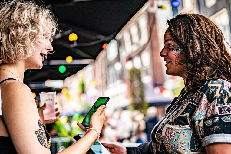 Bezoekers van Club Nyx in Amsterdam met de corona-app. Beeld Joris van Gennip
