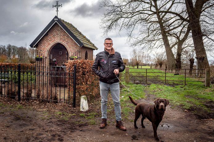 """André van Overveld  bij het kapelletje in de Doeldreef in Wouw waar hij vaak wandelt met zijn hond. ,,Ik heb er de bidprentjes van ma en Saskia opgehangen."""""""