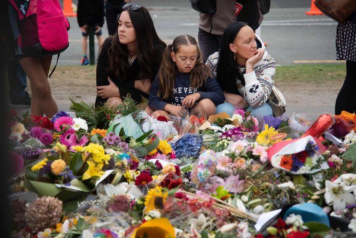 Twee vrouwen en een meisje herdenken de slachtoffers van de schietpartij in Christchurch.