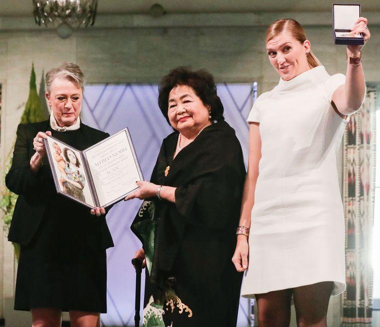 Beatrice Fihn (rechts) en Setsuko Thurlow (midden) nemen de prijs in ontvangst van Berit Reiss-Andersen van het Nobelcomité. Beeld EPA