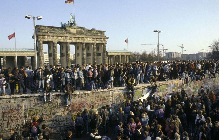 Berlijners op de Muur aan de Brandenburger Tor in het hart van de stad, een dag nadat de grenzen opengingen. Beeld Photonews
