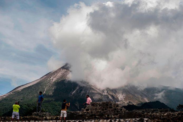 Mensen kijken toe hoe de actieve vulkaan Merapi as spuwt.
