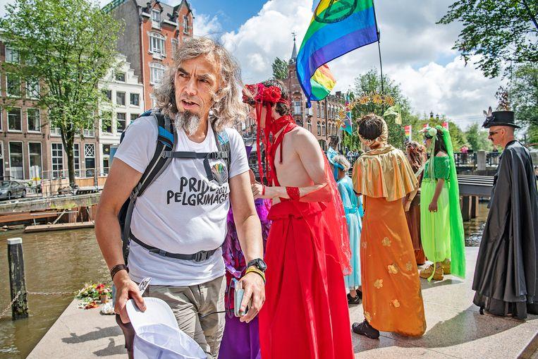 Een deelnemer aan de Pride Pelgrimage, een voettocht van kerkelijke lhbti'ers, op het aankomstpunt van de tocht, het Homomonument in Amsterdam. Op de achtergrond  leden van Extinction Rebellion. Beeld Guus Dubbelman / de Volkskrant