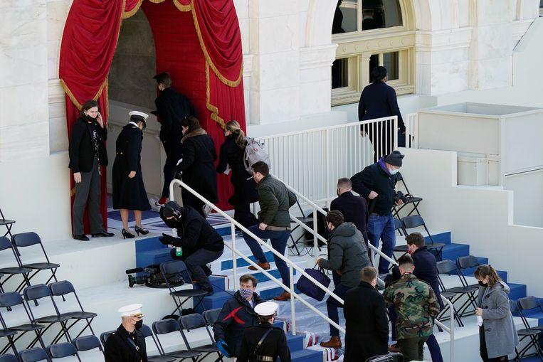 Mensen zoeken een veilige plek tijdens de repetitie voor de inauguratie.  Beeld AP
