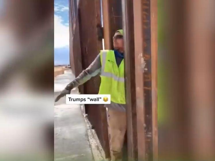 Un ouvrier passe entre les barreaux du mur de Trump