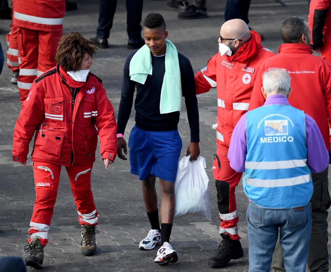 Het Italiaanse Rode Kruis begeleidt een migrant naar de bus.