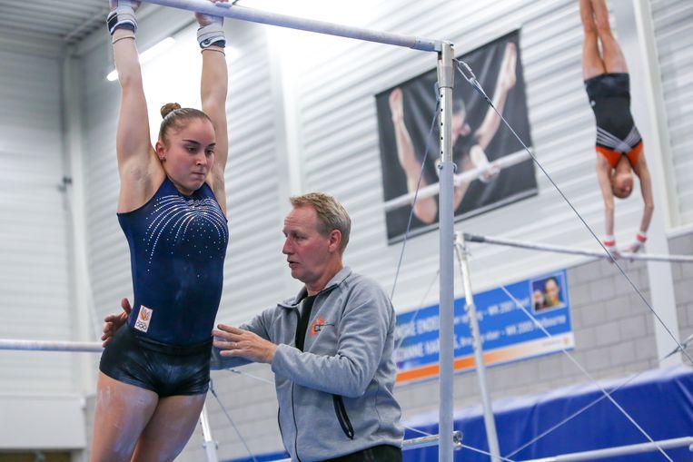 Coach Vincent Wevers, hier aan het werk met Vera van Pol, vraagt het uiterste van turnsters. Of hij daarmee te ver is gegaan, wordt onderzocht. Beeld Getty Images