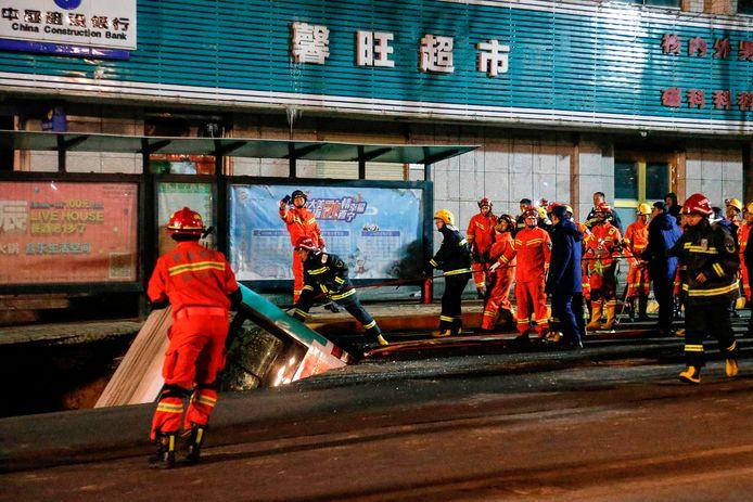 Een bus steekt uit het zinkgat in Xining, voordat het voertuig omhoog wordt getakeld.