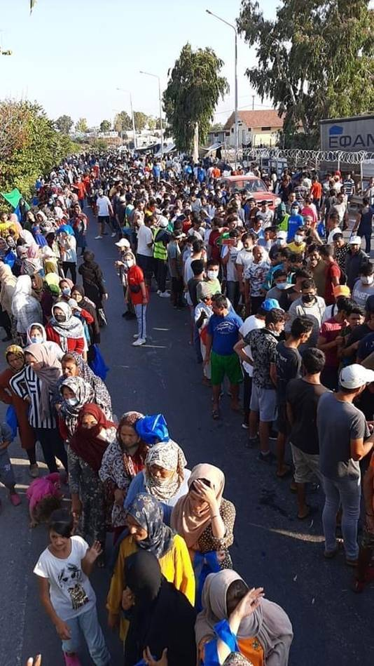 Nabij kamp Moria staat elke dag een kilometerslange rij met vluchtelingen, wachtend op eten en drinken.