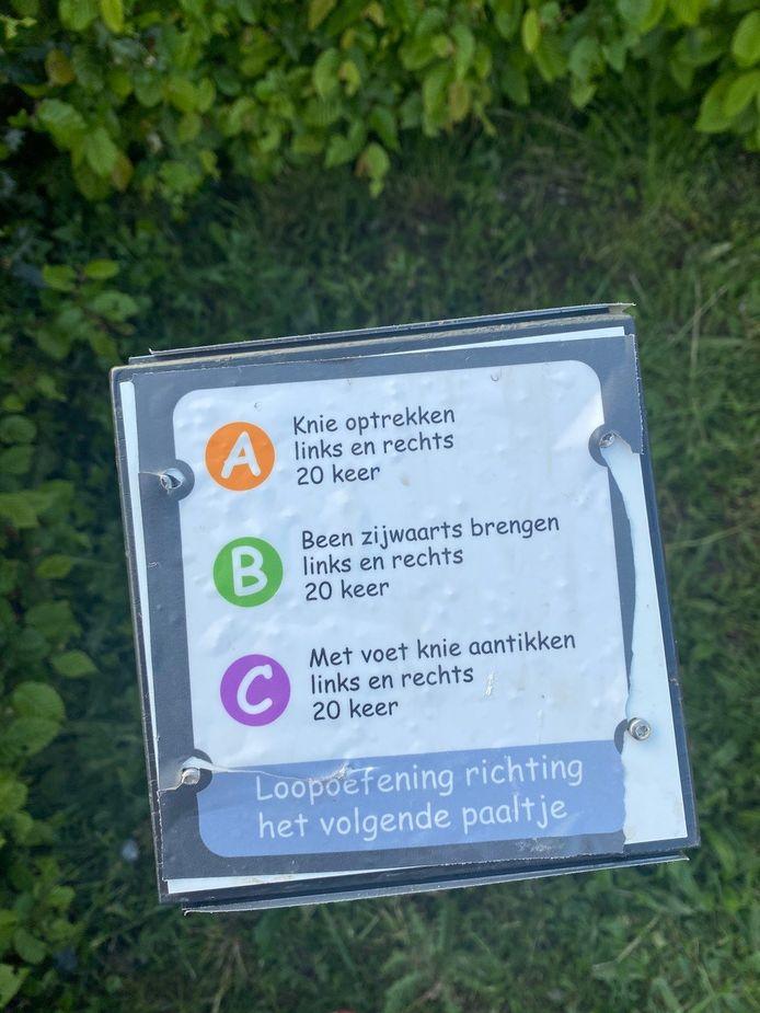 Een van de vernielde bordjes ligt op de grond bij het beweegpark in Molenhoek.