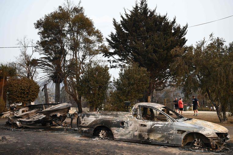 Door het vuur verwoeste auto's en een een boot in Lake Conjola in New South Wales. Beeld AFP