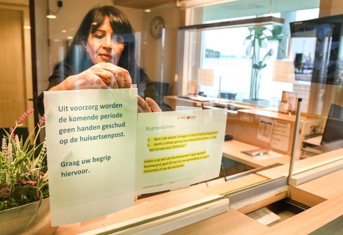 Anet Vos hangt posters op bij huisartsenpost Drechtsteden. Handen worden niet meer geschud vanwege het coronavirus