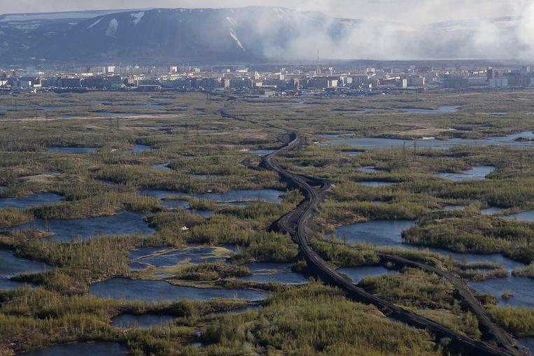 Smeltwater bij de arctische stad Norilsk. Vorige maand vond een olieramp plaats bij Norilsk door het ontdooien van permafrost waardoor leidingen verzakten. De stad, waar nikkel en andere delfstoffen worden verwerkt,  is de grootste luchtvervuiler van Rusland, en stoot twee keer zoveel uit als Londen.  Beeld Kirill Kukhmar/TASS
