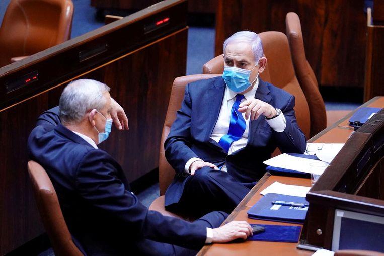 De Israëlische premier Benjamin Netanyahu in gesprek met zijn coalitiepartner Benny Gantz. Beeld via REUTERS