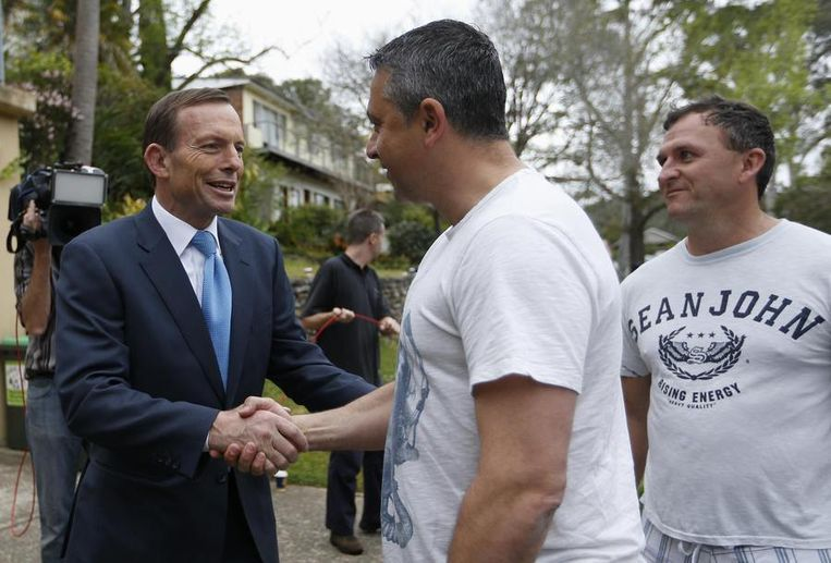 Tony Abbott zondagochtend, daags na zijn verkiezingsoverwinning, bij het verlaten van zijn woning in Sydney. Beeld reuters