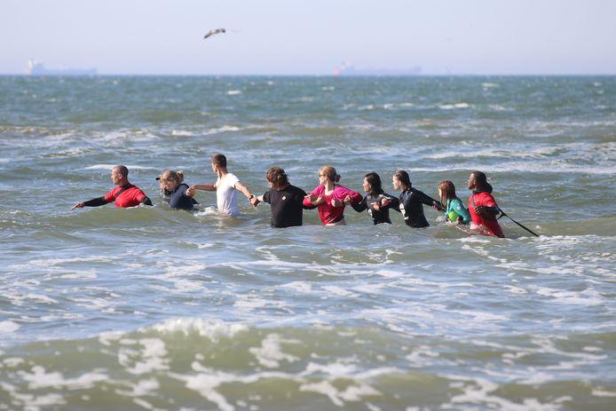Omstanders en hulpverleners hebben een menselijke ketting gemaakt en zoeken in het water.