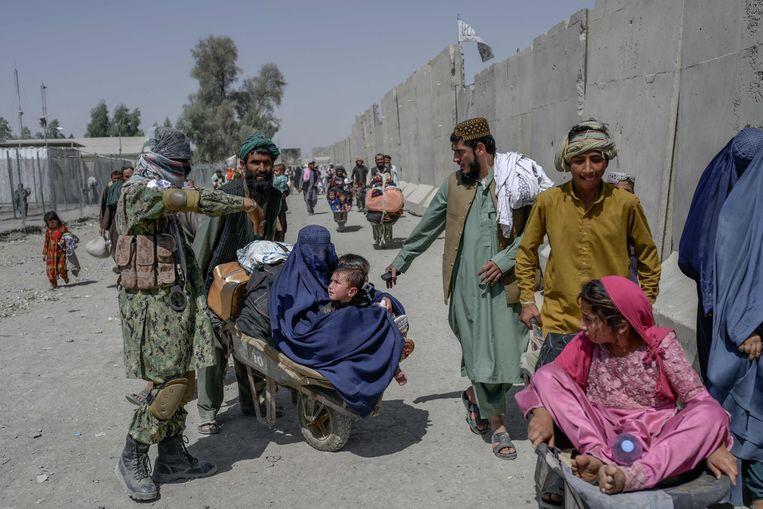 Afghanen bij een grensovergang met buurland Pakistan waar strijders van de Taliban proberen te voorkomen dat de vluchtelingen het land verlaten. Beeld AFP
