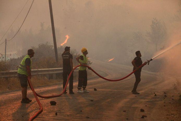 Brandweerlieden, geholpen door inwoners, blussen een brand in de Turkse kuststad Oren.