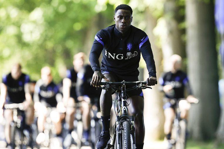 Quincy Promes arriveert op de fiets bij het KNVB-trainingscomplex in Zeist, waar het Nederlands elftal zich voorbereidt voor de  EK-wedstrijd tegen Oostenrijk,  van 17 juni 2021. Beeld EPA