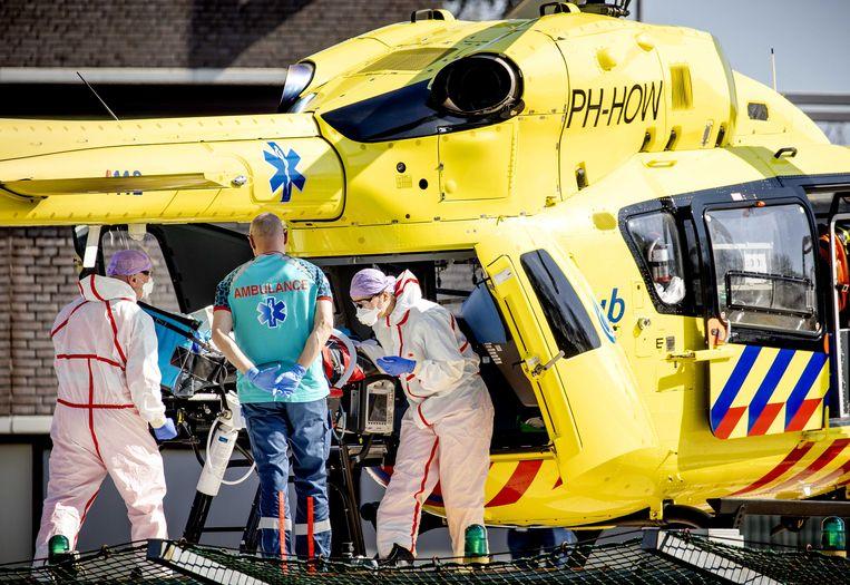Een coronapatiënt wordt een traumahelikopter in gedragen, die naar Duitsland vertrekt vanaf het Elisabeth-TweeSteden Ziekenhuis in Tilburg. Beeld ANP