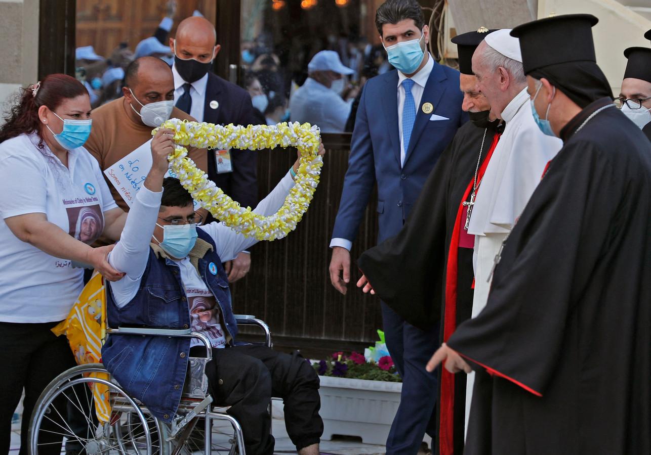 De paus wordt bij de kathedraal onthaald met gezang en een witgele bloemenketting.