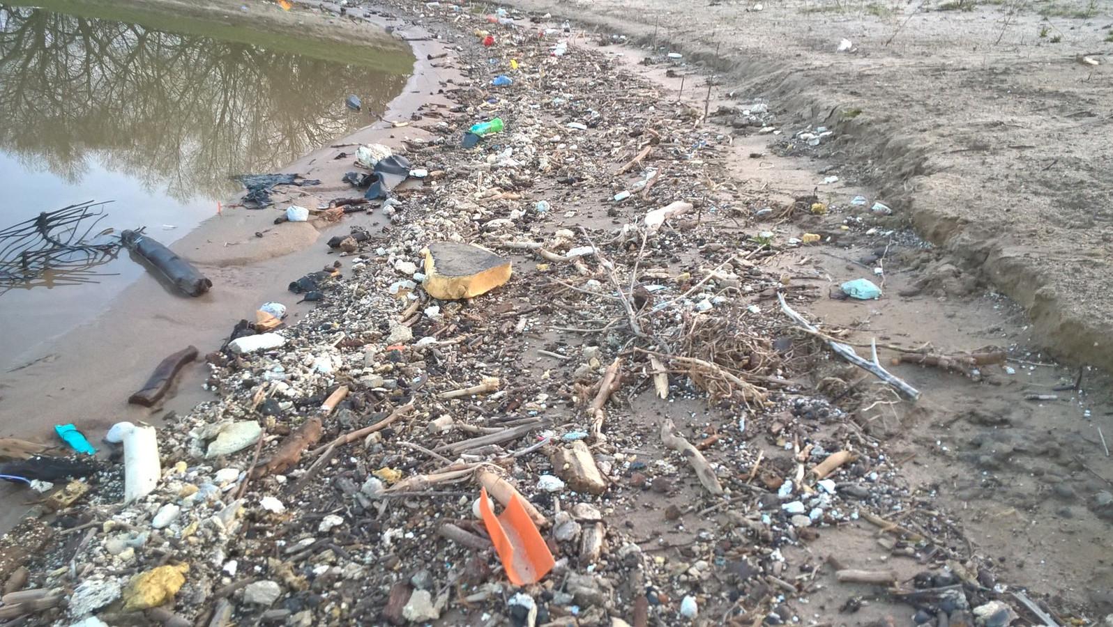 De oevers liggen vol met afval.