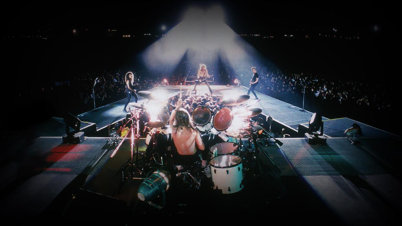 Metallica in concert ten tijde van het 'black album'. Tussen de bandleden in ligt de 'snake pit', waar gelukkige fans mochten plaatsnemen om het concert van dichtbij te volgen. Beeld rv