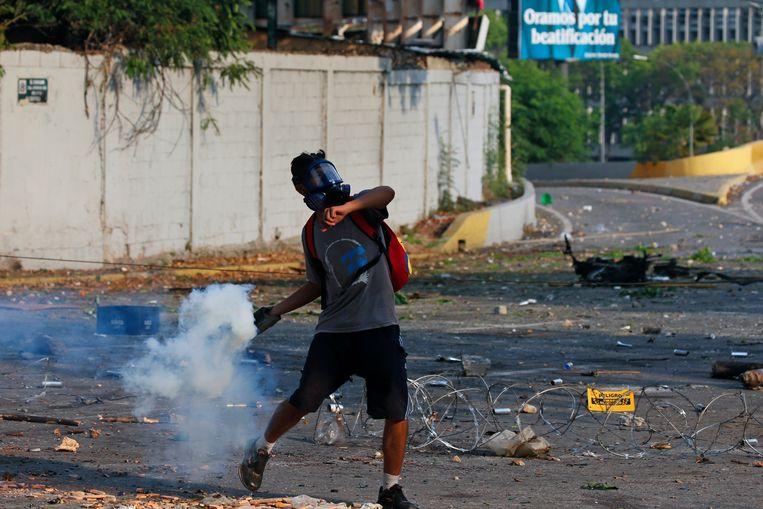 Een aanhanger van Guiado gooit traangas in Caracas. Beeld AP