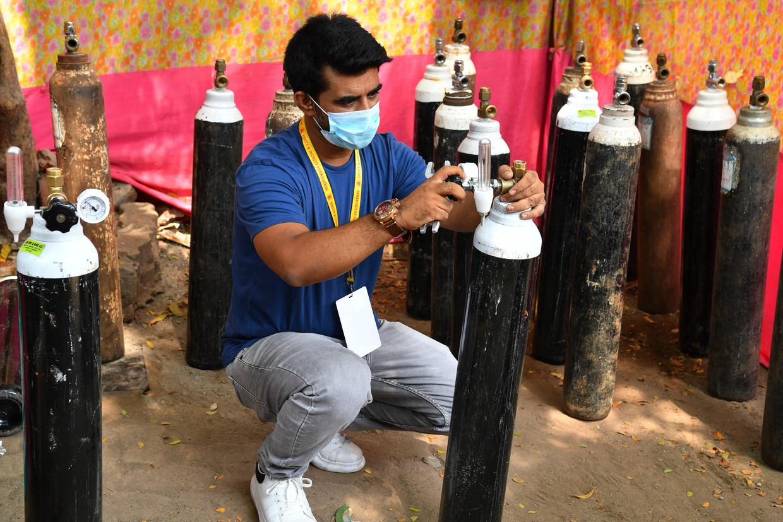 Buurtbewoner Shahnawaz Shaikh vult een van de zuurstofcilinders voor particulier gebruik.