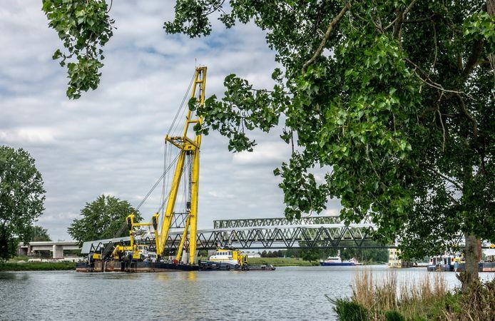 Een grote drijvende kraan brengt de nieuwe fietsbrug naar de plek waar hij wordt ingehesen.