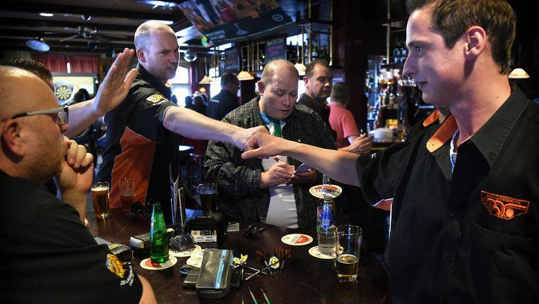 Deelnemers aan de LaCo, de landelijke Dartscompetitie in Nederland. In Café De Swan strijden DONHN en BDC tegen elkaar. Beeld Marcel van den Bergh / de Volkskrant