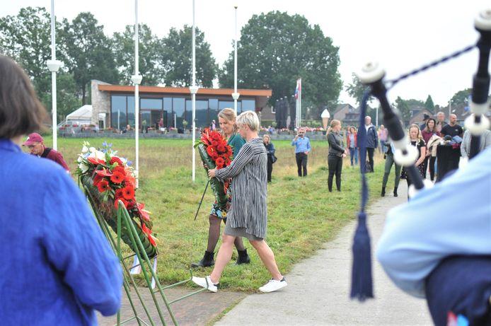 Twee bestuursleden van Renkum Leeft, Janet Bakker en Paula Kuyt, leggen een krans bij het monument op de heide bij Renkum.