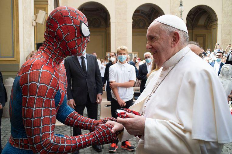 Paus Franciscus schudt een man de hand die als Spiderman optreedt voor kinderen in het ziekenhuis. Het Vaticaan wil dat de kerk op haar eigen manier pastoraal en educatief naar buiten kan blijven treden.  Beeld AFP