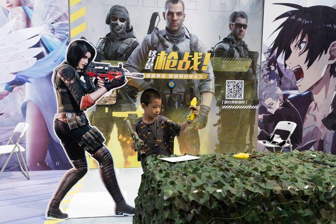 Un enfant joue avec un pistolet jouet lors d'une promotion pour les jeux en ligne à Pékin, le samedi 29 août 2020. La Chine interdit aux enfants de jouer à des jeux en ligne pendant plus de trois heures par semaine, la restriction la plus sévère jusqu'à présent pour l'industrie du jeu, alors que les régulateurs chinois continuent de sévir dans le secteur technologique.