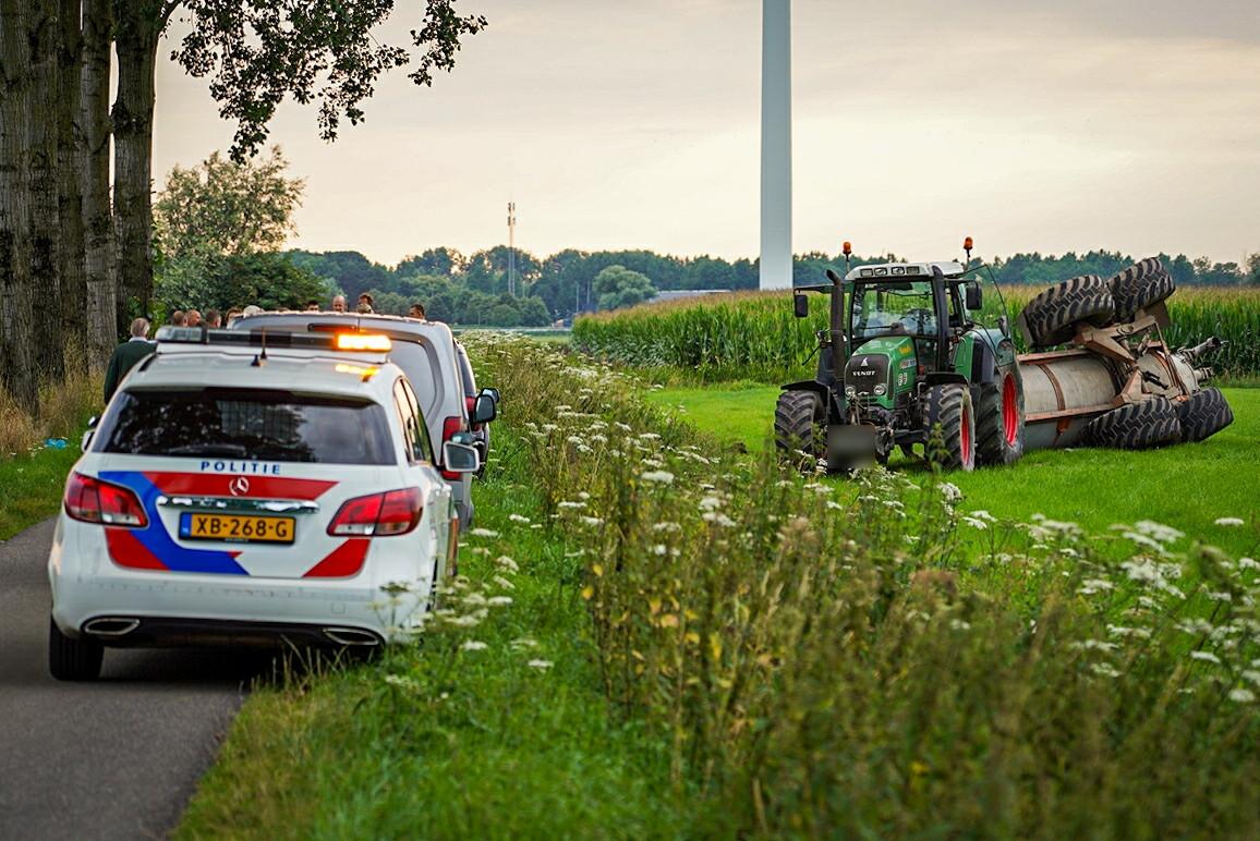 De tractor met de gekantelde watertankwagen in de wei in Duiven.